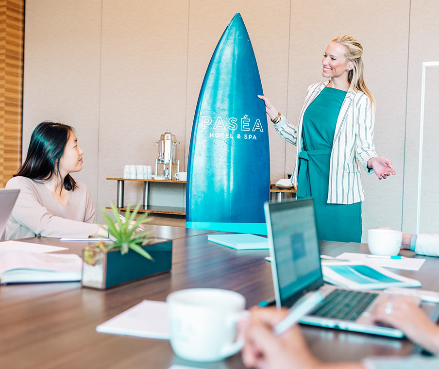 Woman addressing a board meeting holding a surfboard