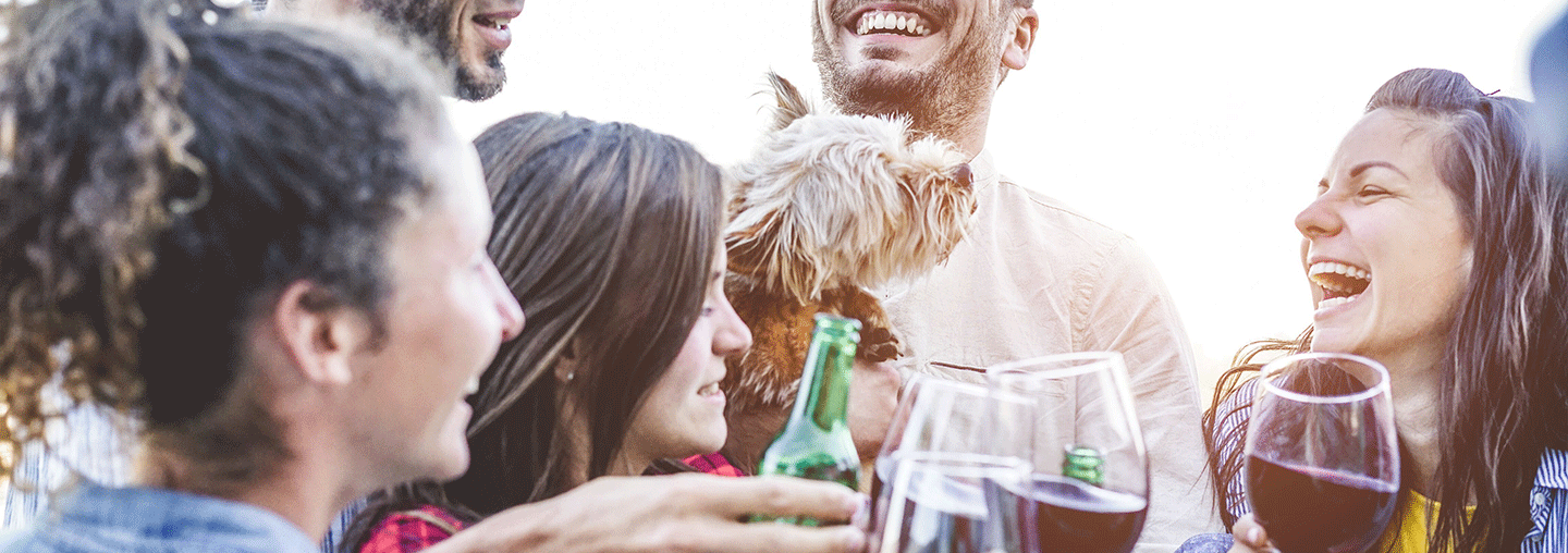 friends toasting with wine while holding a dog