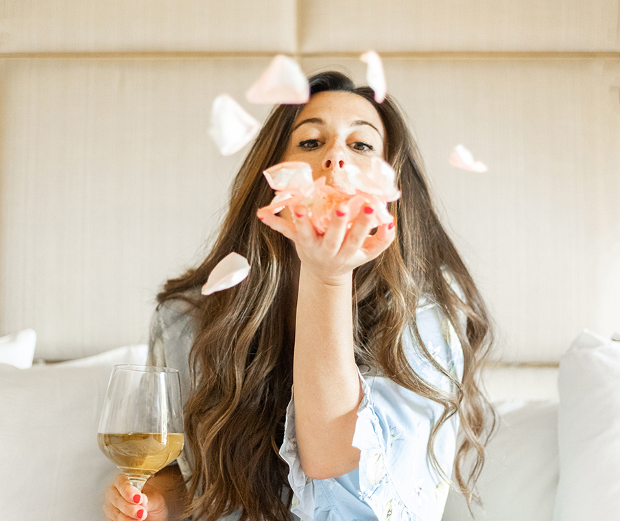 girl blowing rose petals out of hand